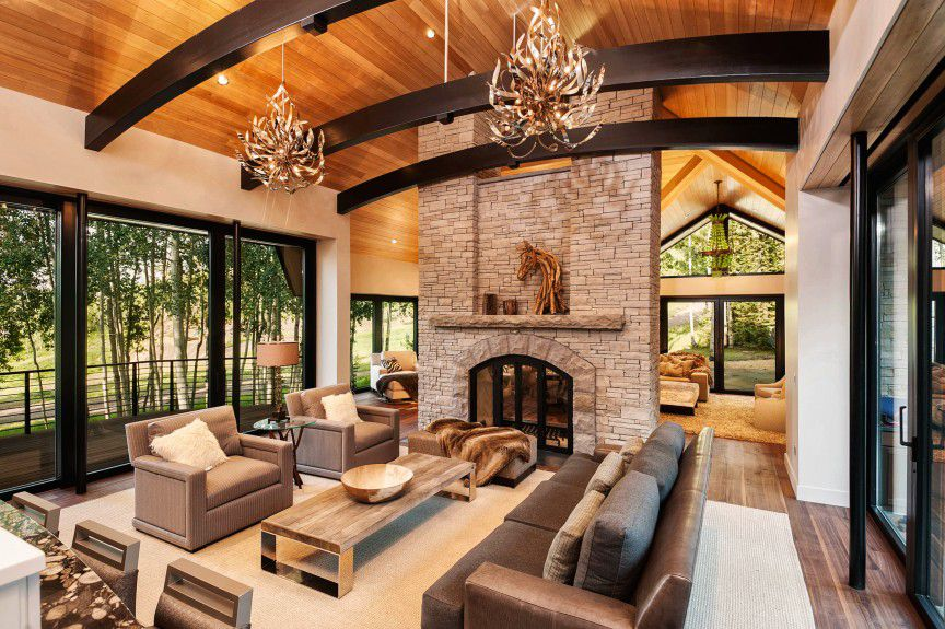 Aspen interior design floor to ceiling stone fireplace between 2 rooms with an